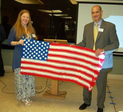 Business card raffle prize winner with prize, a tactile American Flag made by Social Group Activities clients