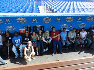 Summer camp students sit in the Miami Marlins dugout.