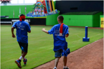 Miami Lighthouse summer camp students running to first base.