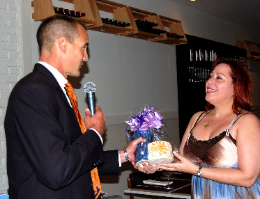 YPOL Co-Chair Agustin Arellano, Jr. presenting Angelique Euro Caf� co-owner Yolanda Rossi with a Lighthouse ceramic made by Miami Lighthouse Social Group Activities clients