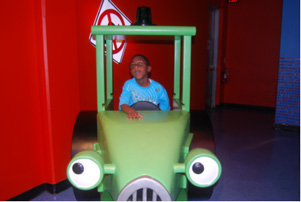 Child rides in a train learning about the different modes of transportation.