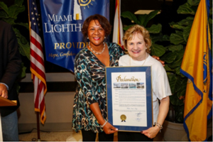 Marie Bell representing Mayor Carlos Gimenez presents Miami-Dade County Proclamation to CEO Virginia Jacko